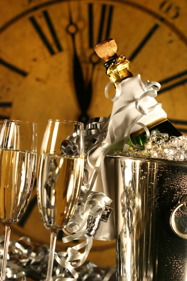 champagne glasses next to a silver bucket with a champagne bottle in it with a big clock in the background
