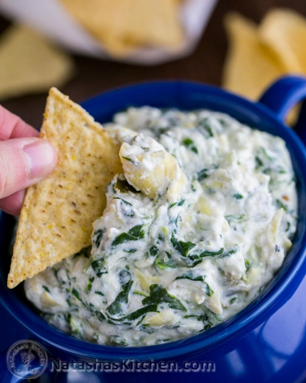 a hand holding a tortilla chip dipped in a blue crock of skinny spinach and artichoke dip