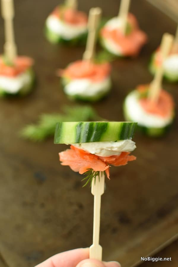 a hand holding a small fork holding a smoked salmon cucumber bites with more of them in the background