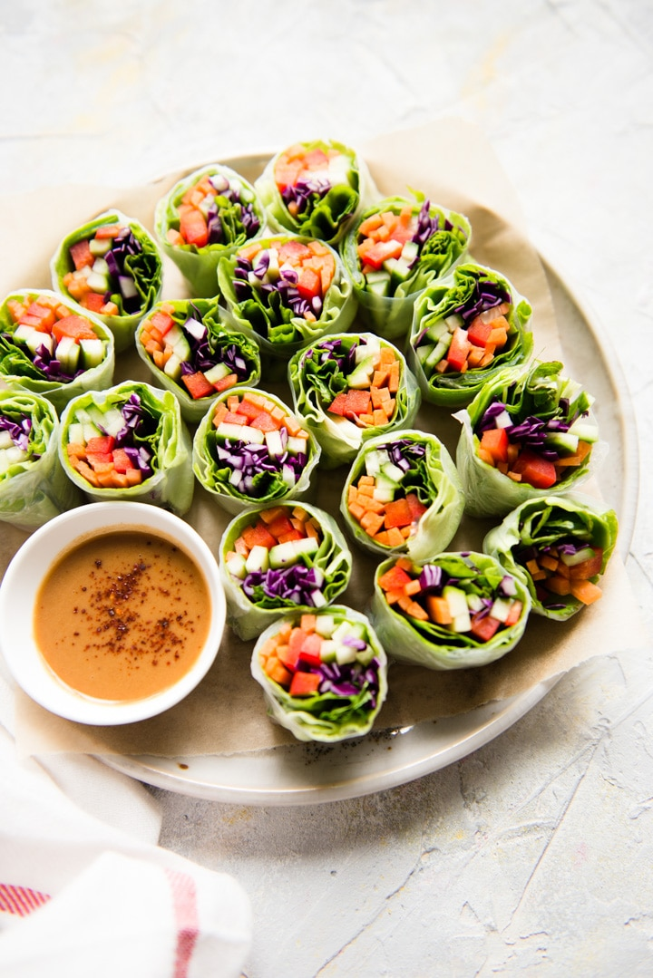 vegan rainbow vegetable spring rolls on a round tray with dipping sauce in a white bowl