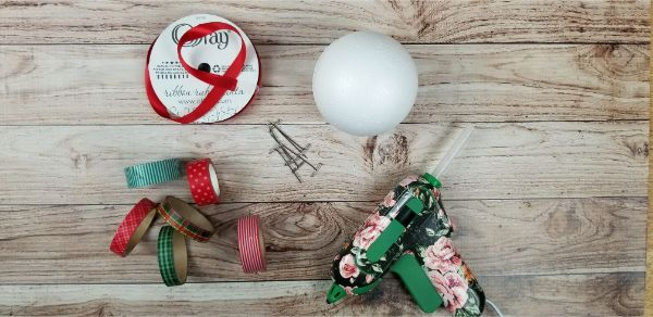 styrofoam ball, washi tape, T pins, red ribbon all on a wood table