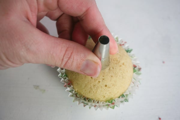 a hand putting a decorating tip over the middle of a cupcake