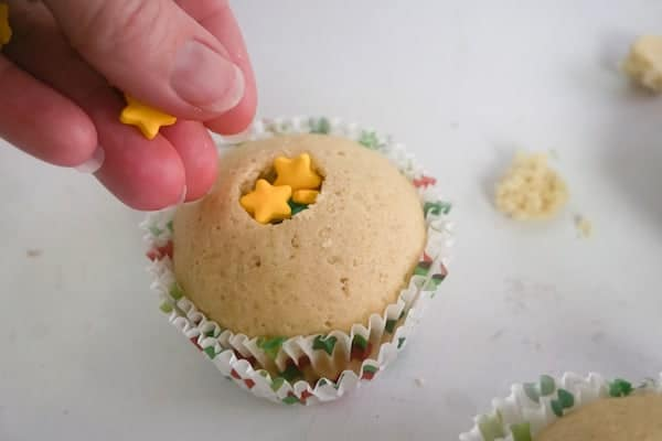 a hand putting star sprinkles in the center of a cupcake
