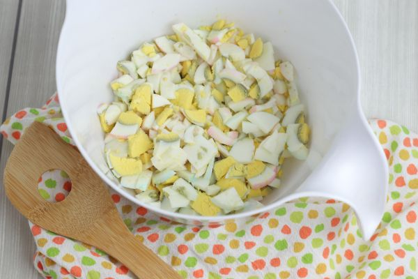 diced hard boiled eggs in a white bowl on a multi-colored linen next to a wooden spoon on a gray wood table