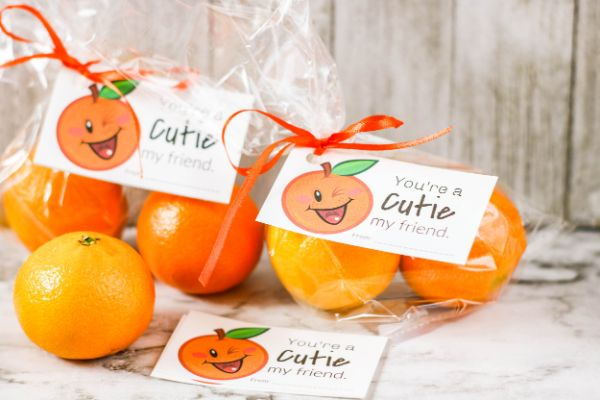 "treat bags filled with cutie oranges with ""You're a Cutie"" gift tag attached with orange curling ribbon with more gift tags and oranges on the counter"