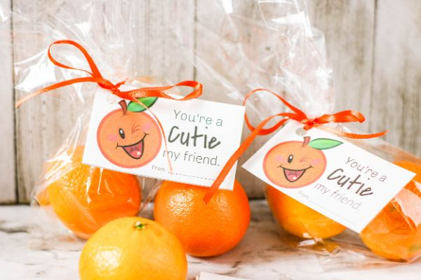 "treat bags filled with cutie oranges with ""You're a Cutie"" gift tag attached with orange curling ribbon with more oranges on the counter"