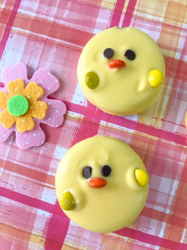 two oreos covered with yellow candy melts decorated with mini chocolate chips for eyes and M&Ms for the beak and wings so they look like Easter Oreo Chicks on a pink and orange cloth next to a felt flower