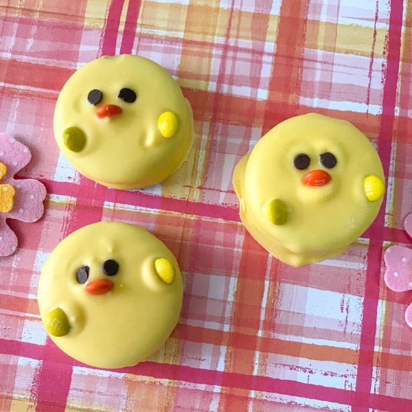 three oreos covered with yellow candy melts decorated with mini chocolate chips for eyes and M&Ms for the beak and wings so they look like Easter Oreo Chicks on a pink and orange cloth next to a felt flower
