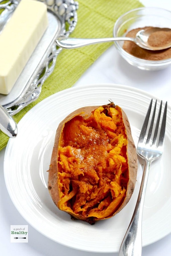 a baked sweet potato on a white plate next to a fork with a spoon in a glass bowl of cinnamon and a tray of a stick of butter in the background on a green and white linen
