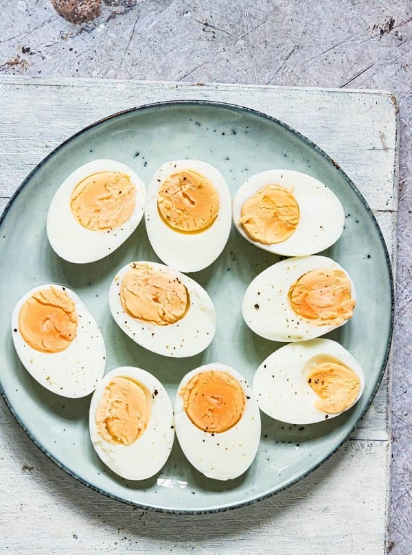 halved hard boiled eggs on a light green plate on a wood table