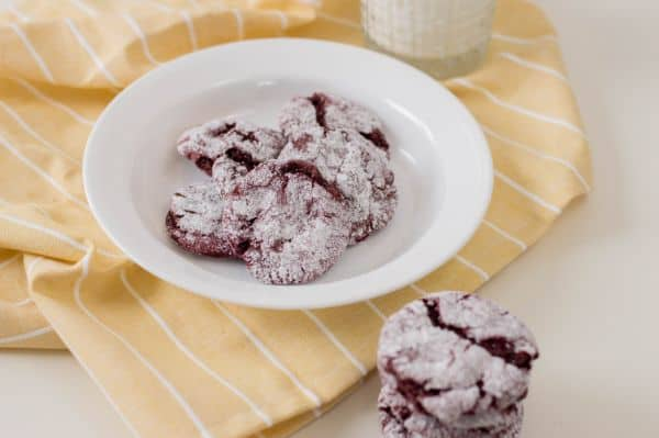 red velvet cookies stacked on a white table with more cookies on a white plate in the background on a yellow cloth next to a glass of milk