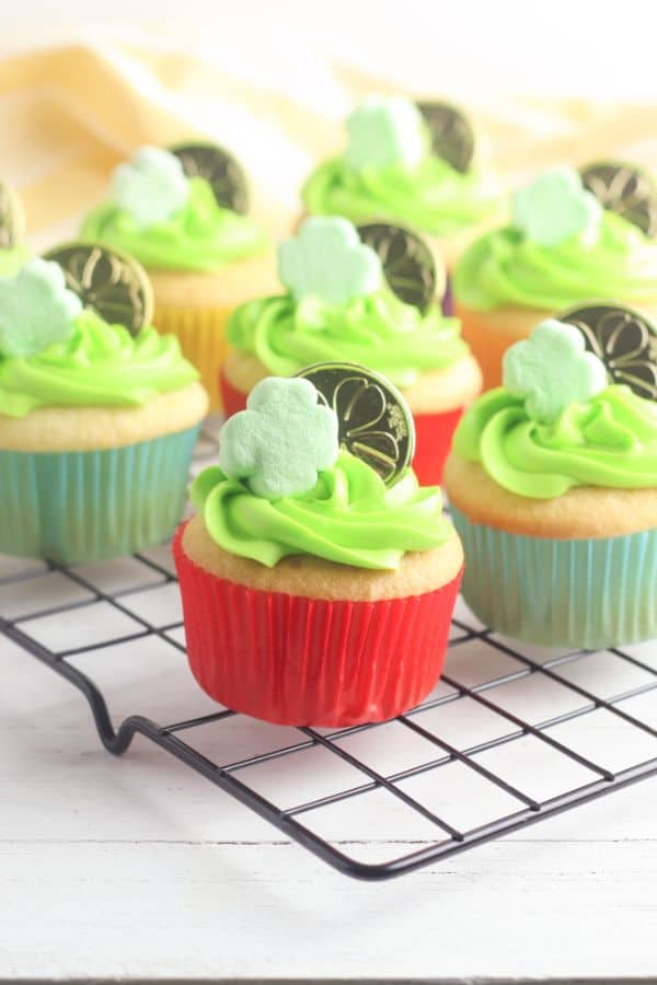 white cupcakes decorated with green frosting, a shamrock marshmallow and gold coin, on a wire rack
