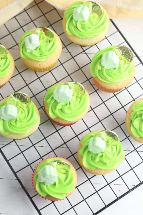 white cupcakes decorated with green frosting, a shamrock marshmallow and gold coin,on a wire rack