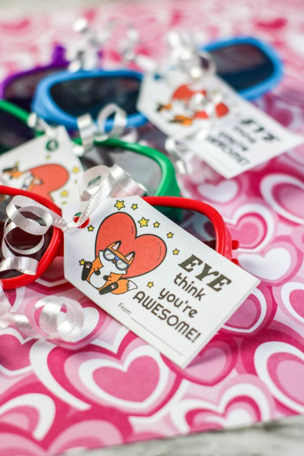 different colored sunglasses with a tag tied to them with white ribbon that reads Eye thing you're awesome, on a heart fabric