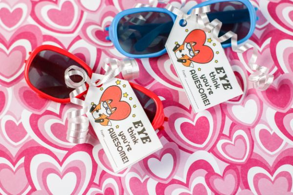 red and blue sunglasses with a tag tied to them with white ribbon that reads Eye thing you're awesome, on a heart fabric