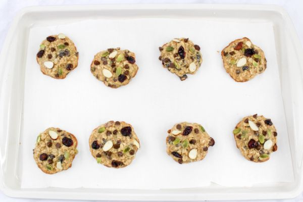 Fresh baked trail mix cookies on white baking sheet