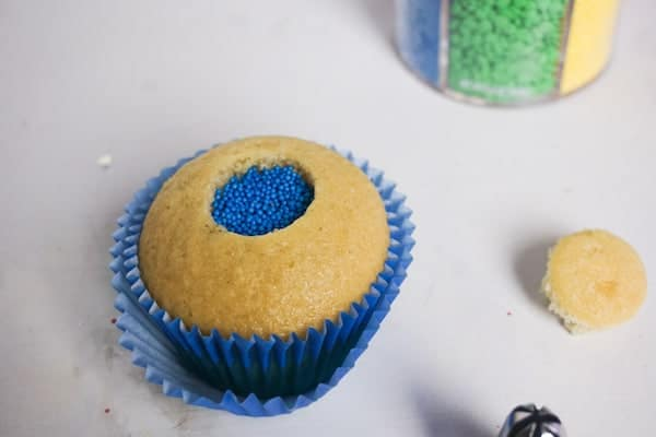 a cupcake with blue sprinkles in the hole in the middle with the rest of the cupcake and a jar of sprinkles in the background