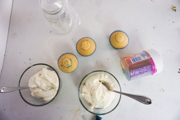 overhead view of three cupcakes, a jar of sprinkles, two glass bowls of frosting with spoons in them