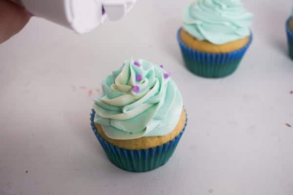 putting purple sprinkles on a cupcake with blue frosting with another cupcake in the background