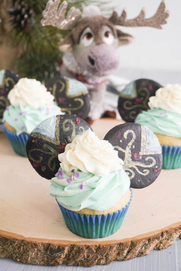 closeup of cupcakes decorated with green ans white frosting and decorated cookies to look like Princess Anna Mickey Ears cupcakes on a log