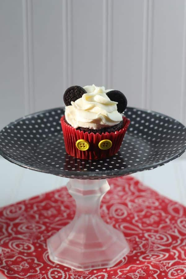 a Mickey Mouse cupcake with oreo ears on a black and white polka dot cake plates on a red and white cloth on a white background