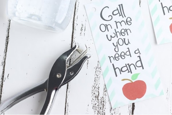 bottle of hand sanitizer, hole punch and printable tags reading call on me when you need a hand, all on a white wood table