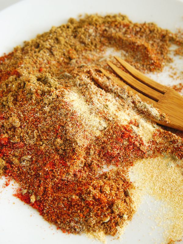 a wooden fork on a plate combining the spices to make easy to make homemade chili seasoning