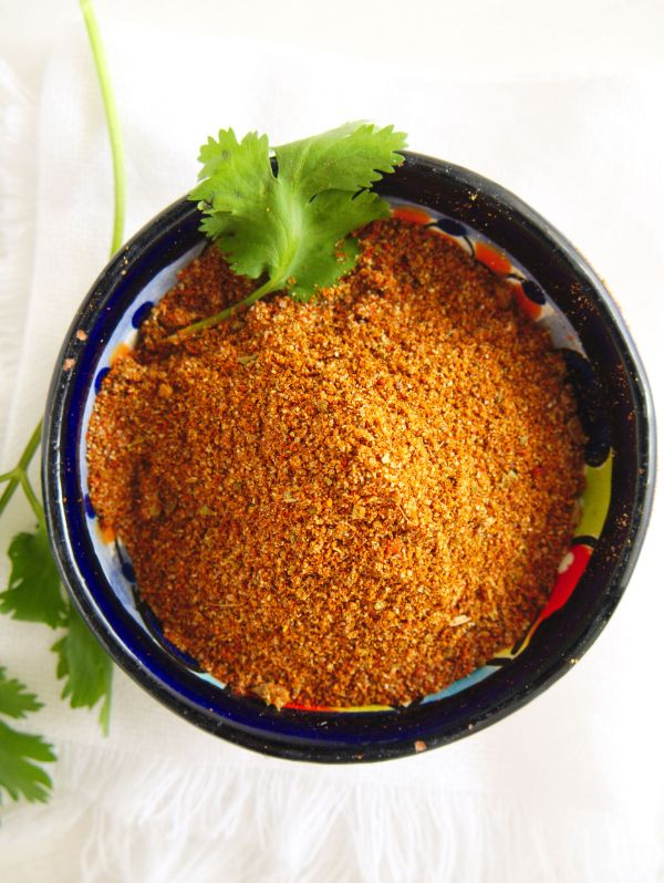 overhead view of easy homemade chili seasoning in a bowl with parsley on it and next to it on a white background