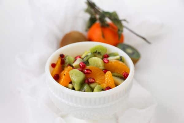 Kiwi Fruit Salad in a white bowl with halved kiwis in the background