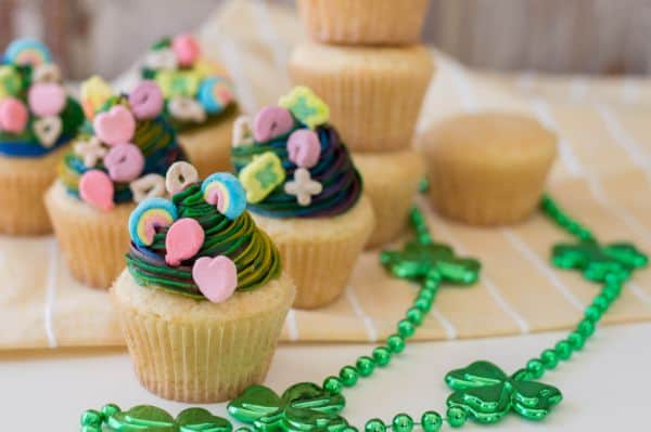 vanilla cupcakes with multi-colored frosting topped with lucky charms marshmallows next to green shamrock beads on a tan linen with stacked vanilla cupcakes in the background