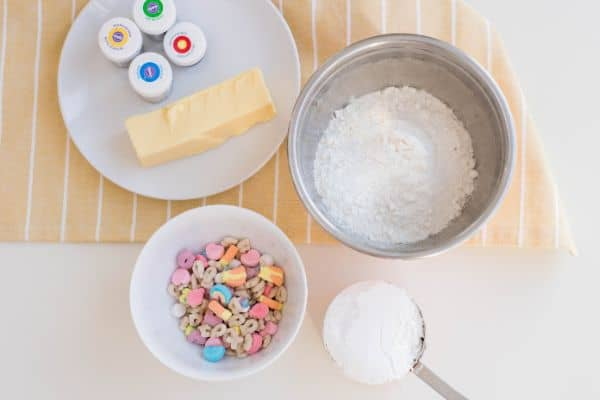 stick of butter and green, blue, yellow red gel food coloring on a white plate, vanilla cake mix in a metal bowl, lucky charms in a white bowl, powdered sugar in a measuring cup, all on a tan linen on a white table