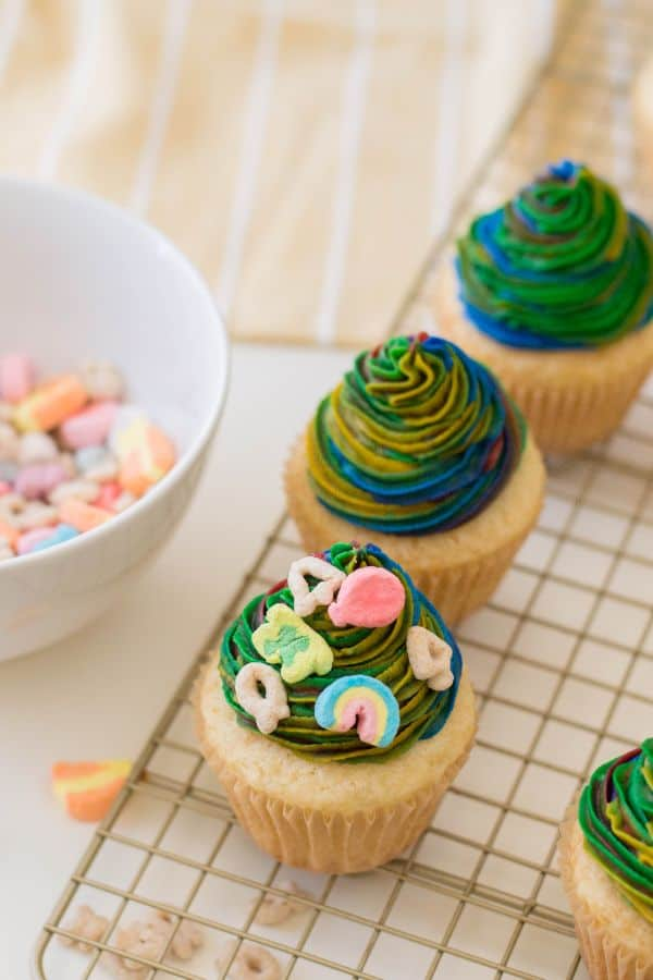 lucky charms in a white bowl, plain vanilla cupcakes and some decorated with multi-colored frosting on a wire rack,  on a tan linen on a white table