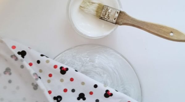 a paint brush on a mod podge can, next to a clear cake plate and Mickey mouse fabric