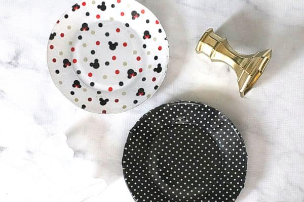 2 cake plates decorated with Mickey Mouse fabric and black and white fabric next to a gold cake stand