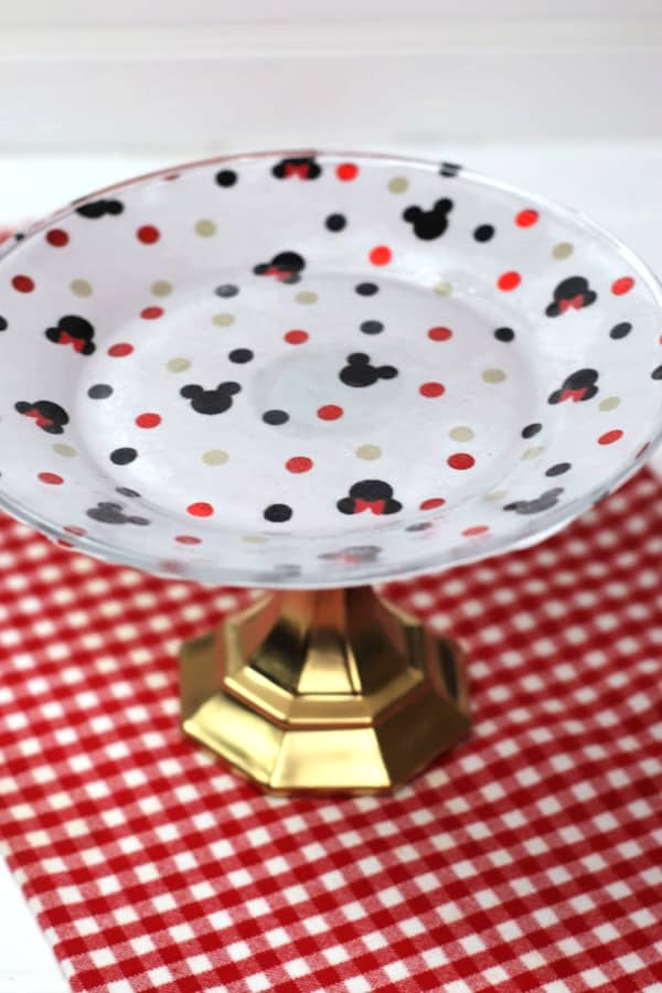 a Mickey Mouse cake plate on read and white checkered fabric