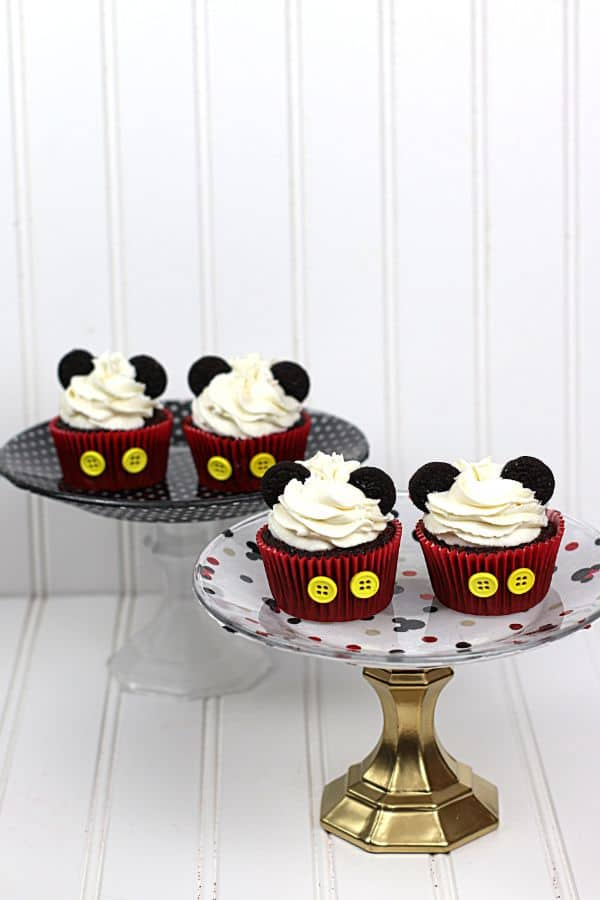 4 Mickey Mouse cupcakes with oreo ears on 2 different cake plates on a white background