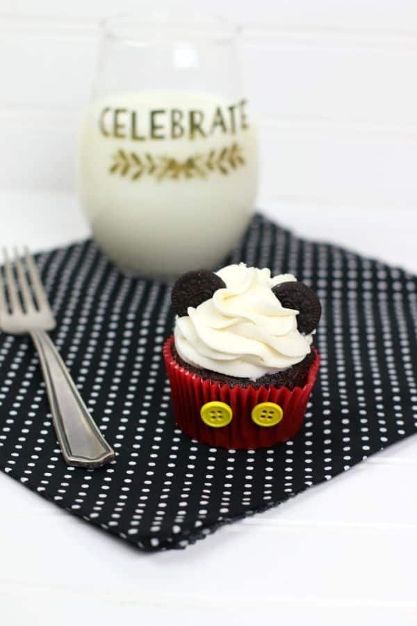 chocolate cupcake decorated with white frosting, mini oreos, and two yellow buttons on the red cupcake liner, to look like Mickey Mouse,  on a black and white polka dot cloth on a white background next to a fork and a glass of milk with the word celebrate on the glass