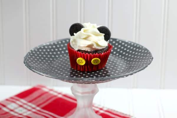 chocolate cupcake decorated with white frosting, mini oreos, and two yellow buttons on the red cupcake liner, to look like Mickey Mouse,  on a black and white polka dot cake plate on a red and white checkered cloth with a white background