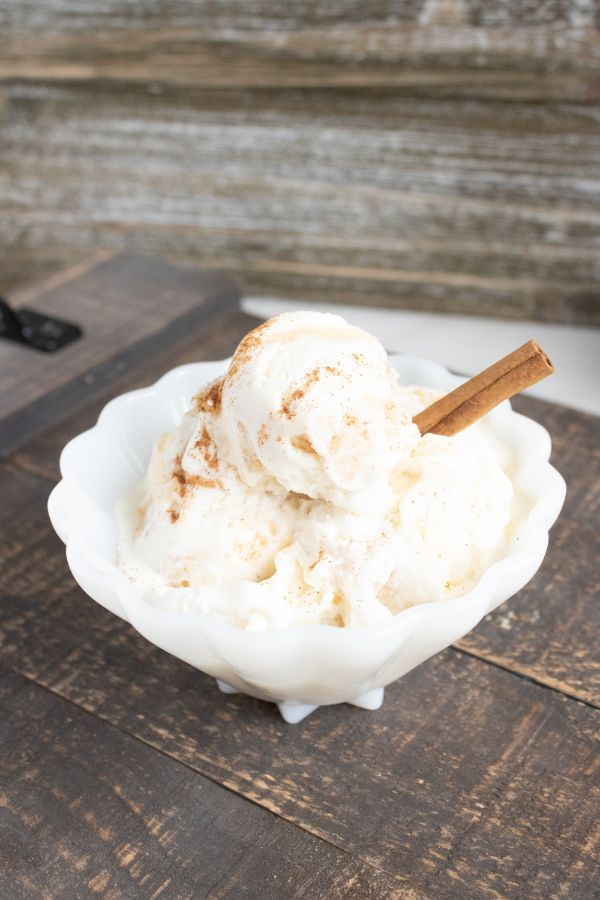 no churn apple pie ice cream with a cinnamon stick in it in a white bowl on a brown table