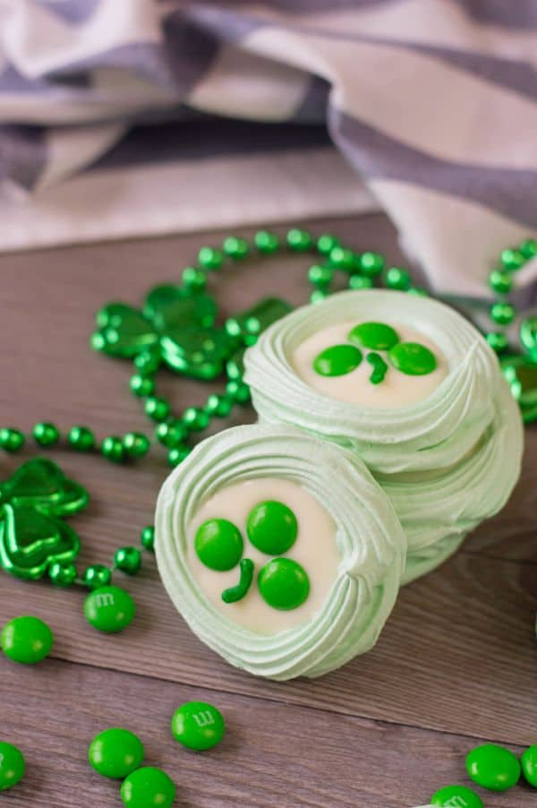 green meringue cookies topped with melted white candy melts, three green m&ms, and a stripe of green frosting to look like a clover, all on a brown table next to green beads with shamrocks on them and more green m&ms with a white and blue striped cloth in the background