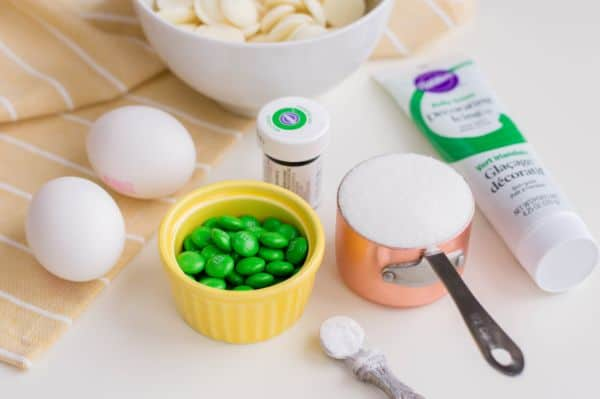 a bowl of white candy melts and two eggs on a peach colored cloth next to green decorating frosting, green food coloring, green m&ms in a yellow bowl, sugar in a measuring cup, and cream of tartar in a 1/4 teaspoon, on a white table