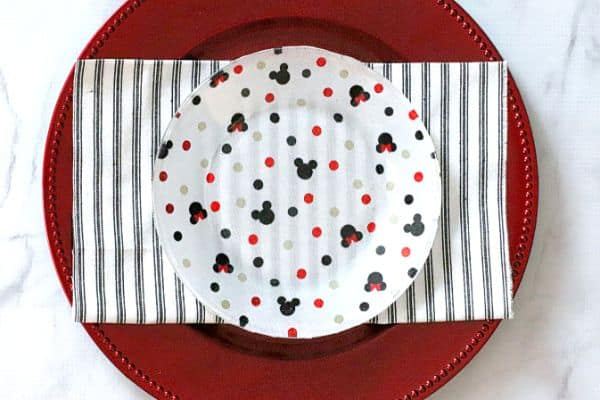 a Mickey Mouse cake plate on black and white babric on a red plate
