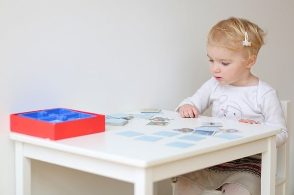 Child Playing Memory game on a white table