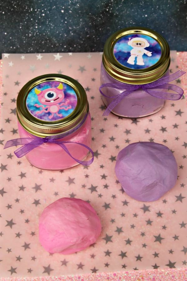 pink and purple Edible Outer Space Play Dough on a pink star paper and in two jars with alien stickers on the lids