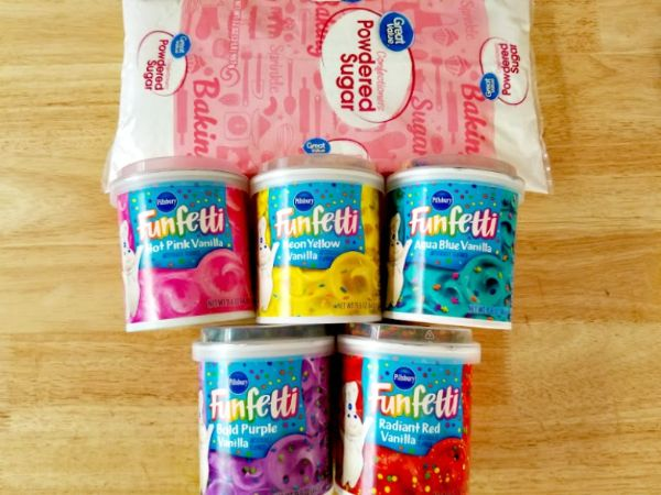ingredients for edible play dough on a brown table, a bag of powdered sugar, 5 cans of different colored funfetti frosting