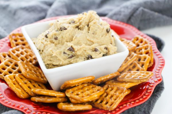 Eggless Chocolate Chip Cookie Dough in a white dish surrounded by pretzels on a red plate on a gray cloth