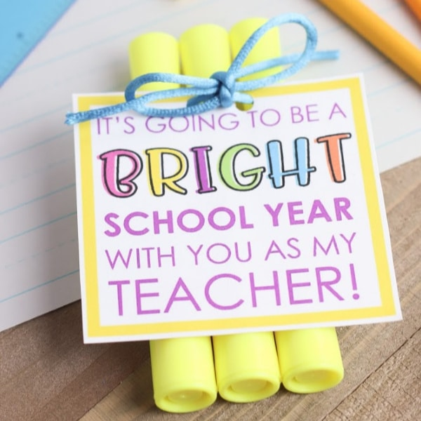 3 yellow highlighters with a gift tag reading it's going to be a bright school year with you as my teacher, with notebook paper, crayons and a ruler in the background