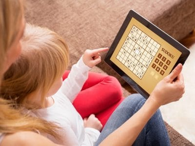 Mother and daughter playing game on tablet computer