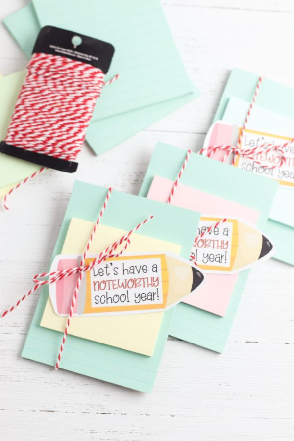 teacher notebook gift of notebook paper, a sticky note and a paper shaped like a pencil with the words Lets have a noteworthy school year on it, all tied together with red and white string