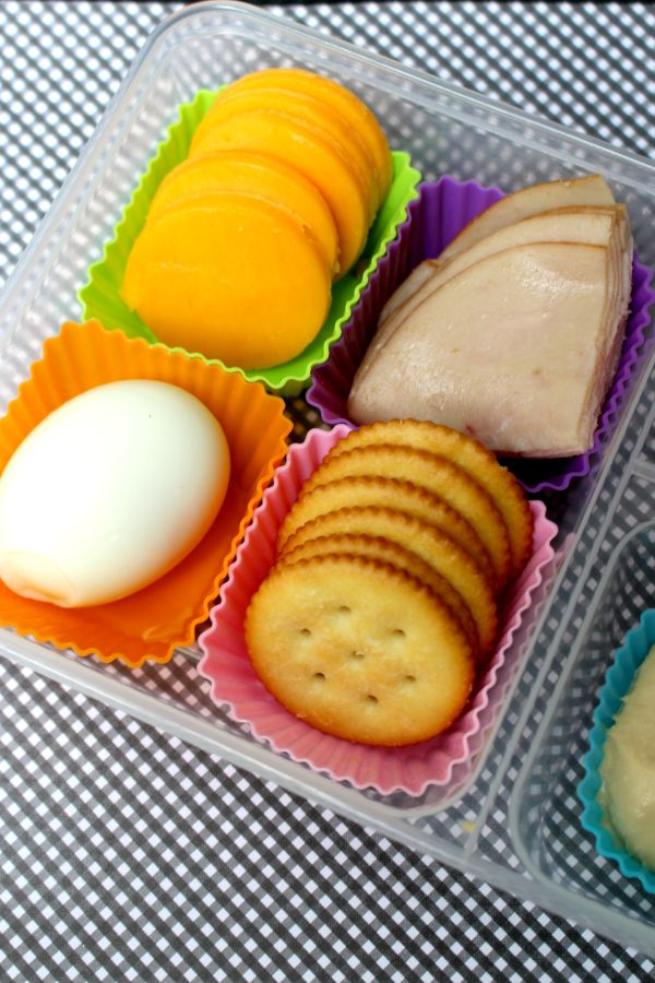 protein lunch box with a hard boiled egg, sliced cheese, crackers and lunchmeat